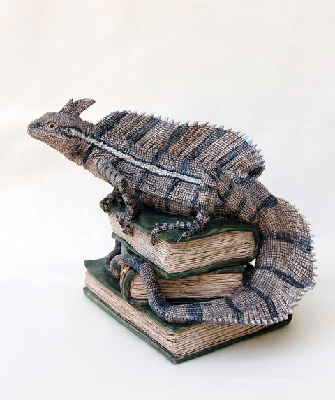 """Brown basilisk on ancient books"" stoneware ceramic by Jill Moger"